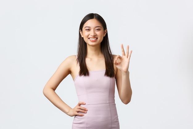 고급 여성, 파티 및 휴일 개념. 이브닝 드레스에 만족 웃는 아시아 여자, 괜찮아 기호 표시 및 승인에 끄덕임, 우수한 제품 평가