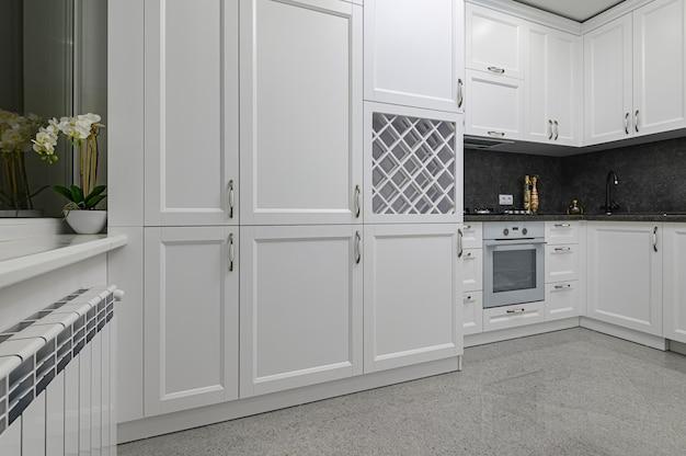 고전적인 스타일의 현대적인 흑백 주방에서 고급 목재 가구