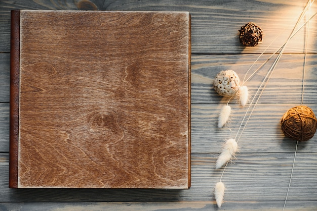 Luxury wooden photo book on natural background. family memories photobook. save your summer vacation memories. photo album wedding photoalbum with wooden cover.