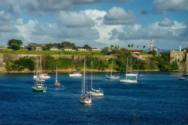 Роскошные яхты на якоре в голубой воде с фортом на заднем плане.
