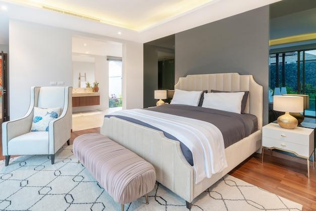 Недвижимость luxury дизайн интерьера спальни виллы с бассейном с уютной двуспальной кроватью.