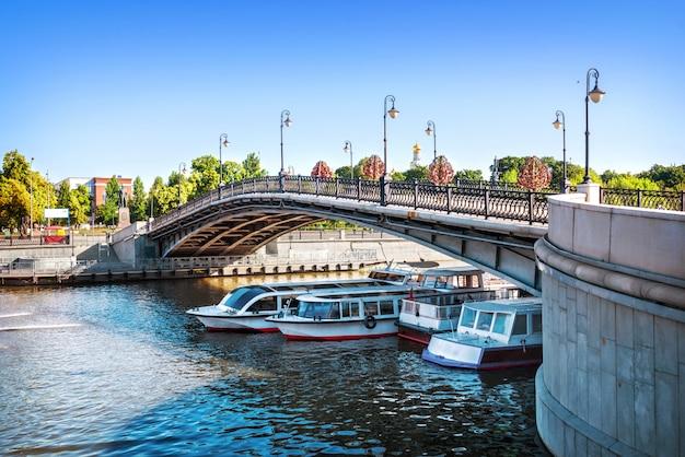 Лужков мост через водоотводный канал в москве и третьяковская пристань с кораблями под мостом солнечным летним утром