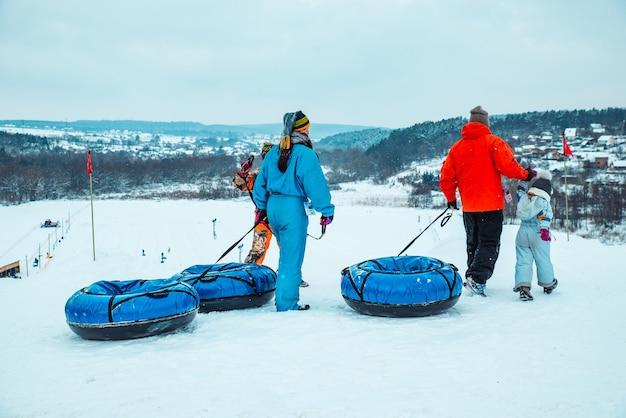 ウクライナ、リヴィウ-2019年1月7日:家族はスノーチューブで雪の丘を下ります。冬時間