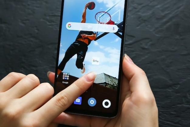 Lviv, 우크라이나 - 2019년 10월 30일: 최신 스마트폰 화면에서 google pay 애플리케이션 아이콘을 선택하는 스마트폰 사용자