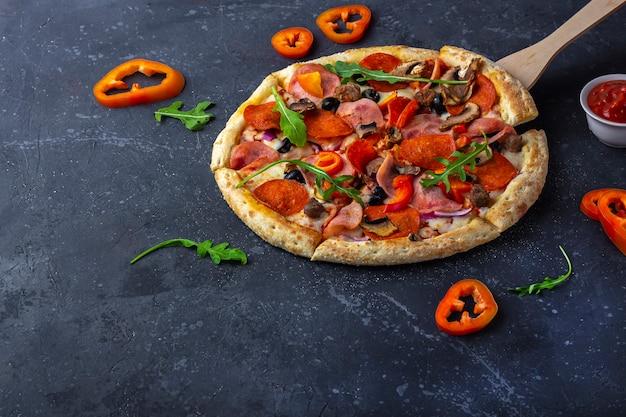 暗い背景にサラミ、マッシュルーム、ハム、チーズを加えた新鮮なピザ。イタリアの伝統的なランチまたはディナー。ファーストフードとストリートフードのコンセプト。フラットly、トップビュー、コピースペースfotテキスト