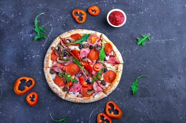 暗い背景にサラミ、マッシュルーム、ハム、チーズを加えた新鮮なピザ。イタリアの伝統的なランチまたはディナー。ファーストフードとストリートフードのコンセプト。フラットly、トップビュー