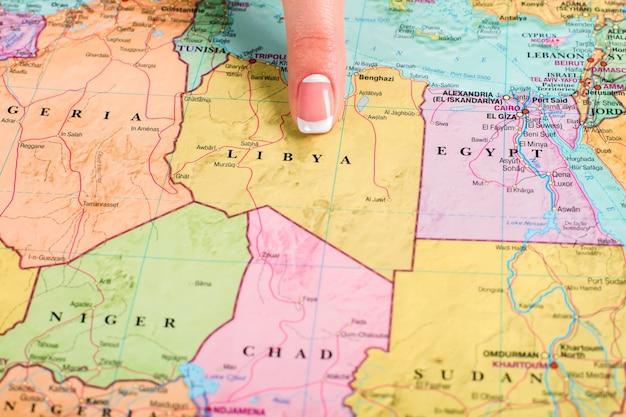 리비아에서는 세계 지도입니다. 리비아를 가리키는 여성의 손가락. 갈등을 일으키기 쉽습니다. 불안정한 지역은 범죄의 보물입니다.