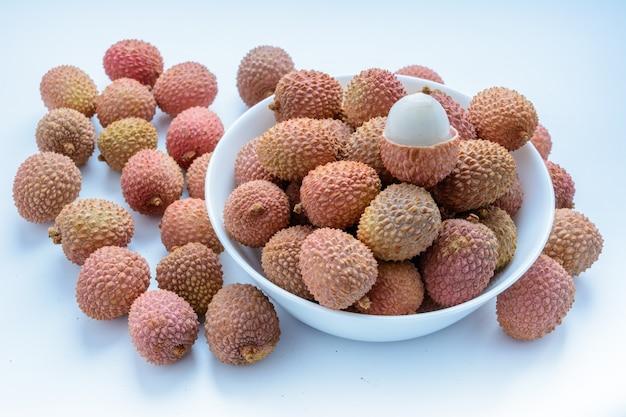 열매(lee-chee; litchi chinensis)는 솝베리과의 litchi 속의 유일한 구성원인 sapindaceae입니다. 열매는 흰색 배경에 접시에 있습니다. 껍질이 없는 익은 리치. 열대 과일.