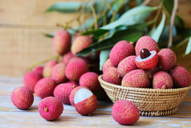 Lychee slice peeled on wooden. fresh lychee with green leaves harvest in basket from tree tropical fruit summer in thailand