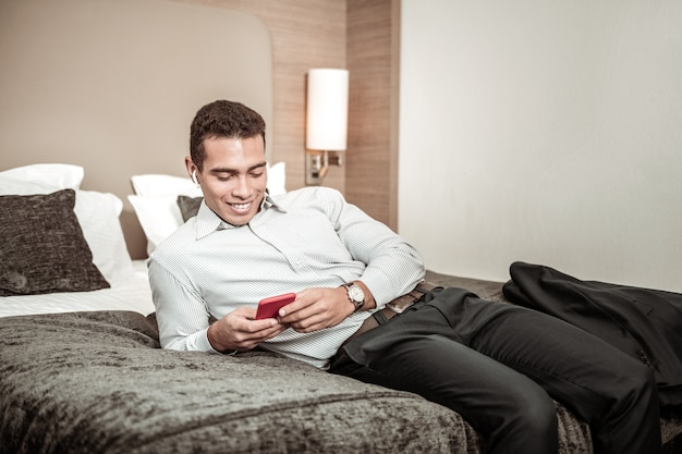 Lying on bed. businessman lying on hotel bed and chilling using phone after long and tiring flight