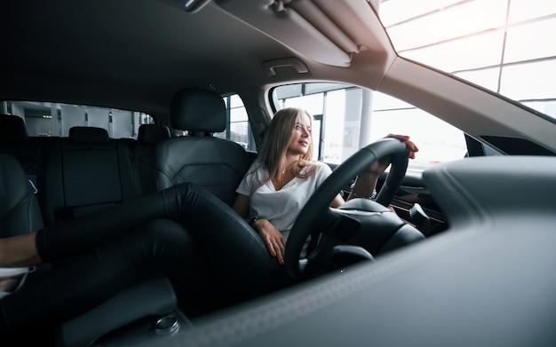 席に横になる。サロンで現代の車の女の子。昼間の屋内。新しい車を買う