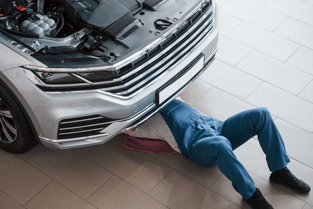 Lying down on the pink colored towel. man in blue uniform works with broken car. making repairings.