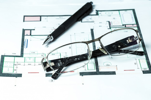 Lying glasses on a schematic plan of interior design