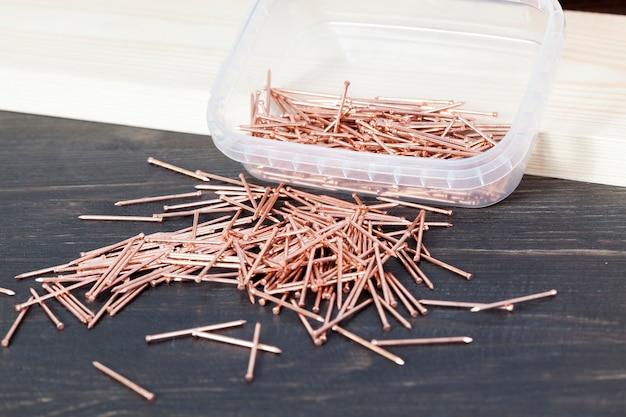 Рядом с деревянной доской лежат красные медные гвозди для отделки деревянных конструкций.