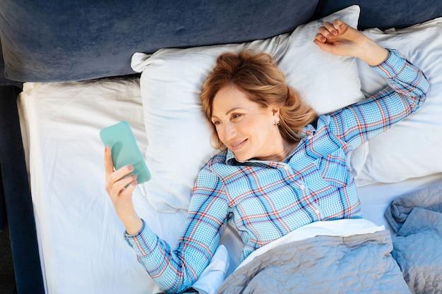 枕の上に横たわっています。彼女の背中に横たわって、早朝に携帯電話を持って笑顔のポジティブな大人の女性