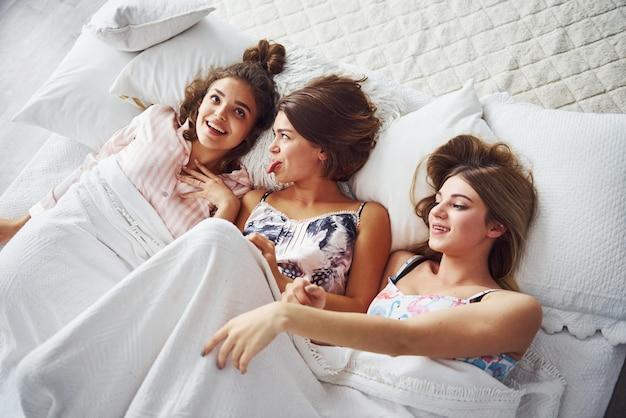 Вместе лежат на кровати под одеялом. счастливые подруги хорошо проводят время на пижамной вечеринке в спальне.