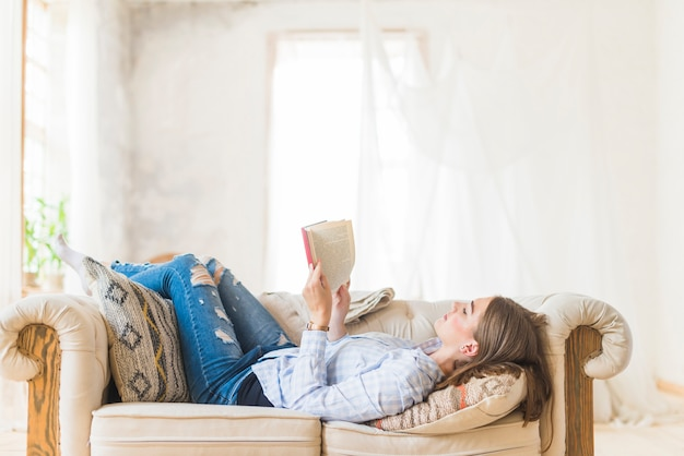 Lying woman reading novel on couch