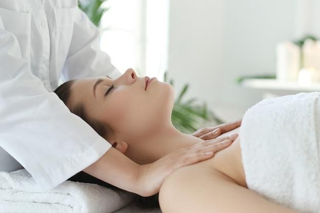 Лежащая женщина получает массаж тела.