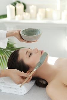 Лежащая женщина, получающая косметические процедуры для лица.