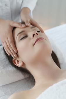 マッサージを受けて横になっている女性。頭蓋仙骨療法