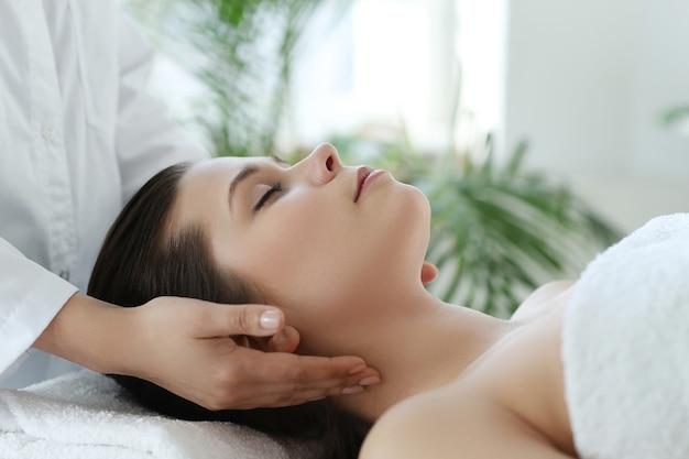 Лежащая женщина, получающая массаж. краниосакральная терапия