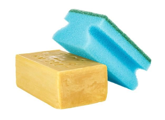 Лежащее желтое хозяйственное мыло с синей губкой для мытья посуды сверху, изолированные на белом фоне