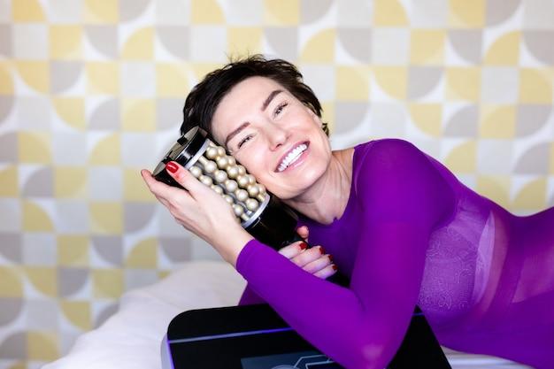 Лимфодренажный массаж аппаратный процесс. женщина в белом костюме получает антицеллюлитный массаж