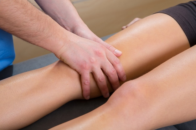 Lymphatic drainage massage therapist hands on woman leg