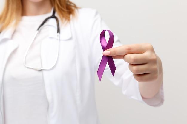 Концепция лимфомы. фиолетовая лента в изолированной руке.