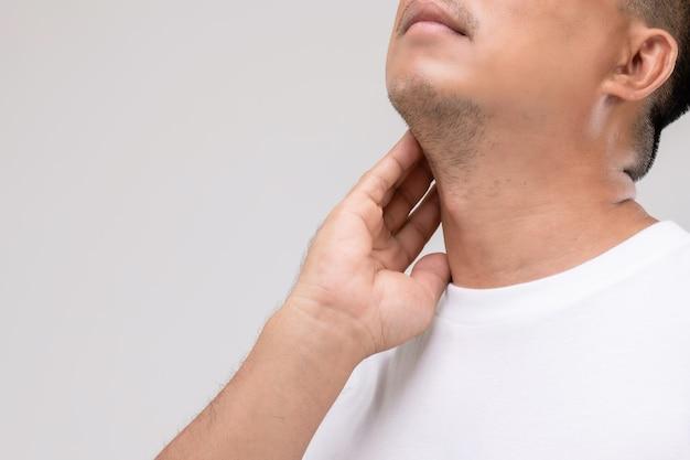男性のリンパ腫の概念:肖像画アジア人男性がリンパ節の位置で首に触れています。