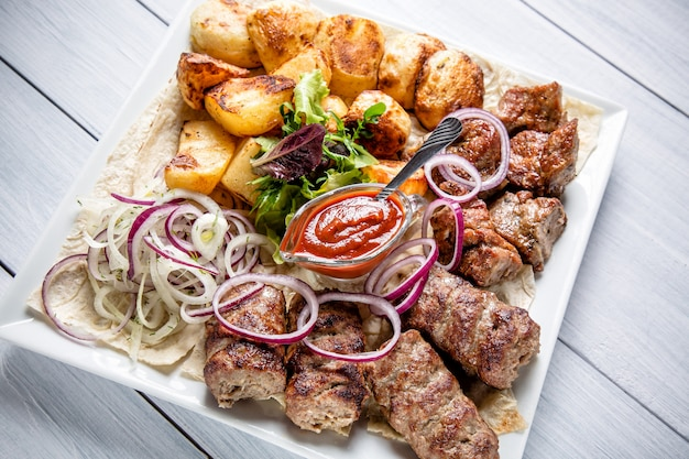 Lyulya kebab with red sauce, onion and potatoes on white plate