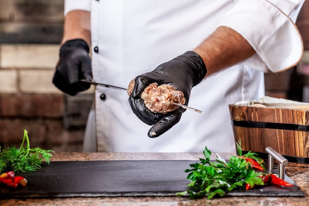 グリルの生地で肉lyulyaケバブを調理するシェフ。