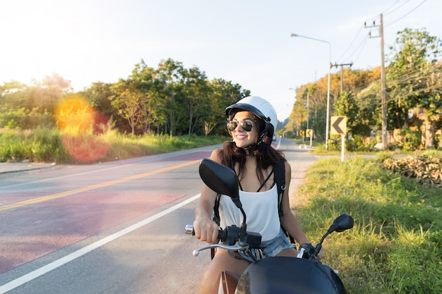Mの魅力的な女性は田舎道でhelemtを着用します。mのきれいな女性オートバイ旅行