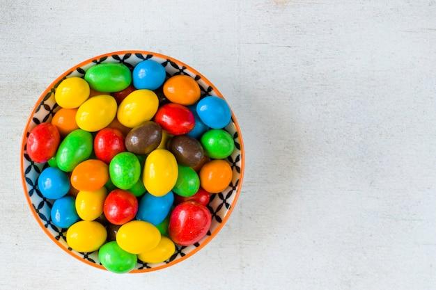 白い背景のボウルにあるm&mのキャンディー、カラフルなキャンディーの質感、色とりどりのグラデーション。