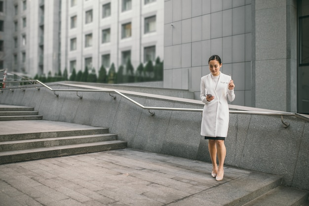 メガネで笑顔の魅力的なアジアビジネスの女性は、オフィスセンターmの近くの手すりの同僚に傾いた新聞を読んでいます。