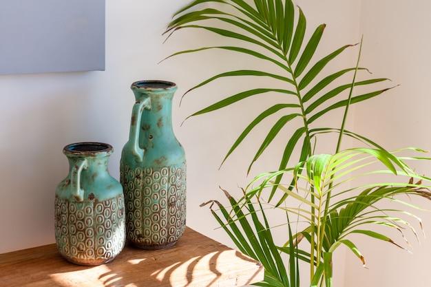 日光居心地の良いホームシーンで木製のテーブルとma下ヤシの2つの装飾的なつぼ