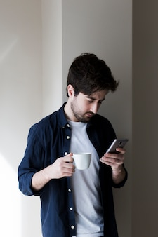 Ma drinking and using smartphone during break