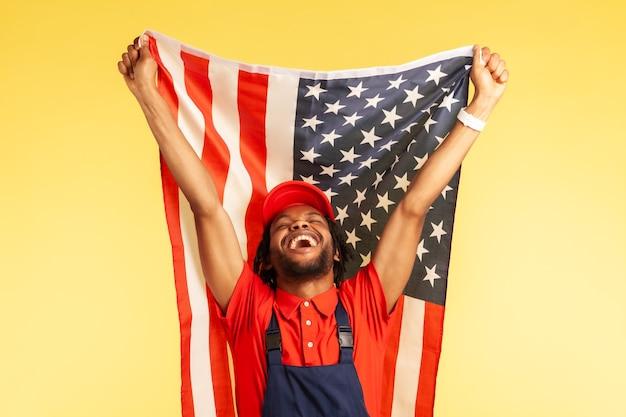 Ма держит флаг соединенных штатов америки, празднуя день независимости сша