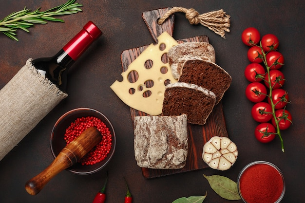Maasdam cheese sliced on a cutting board with cherry tomatoes, black bread, garlic and rosemary, bottle of wine