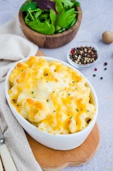 Макароны с сыром. традиционные запеченные макароны с сыром в форме для запекания. американская кухня. вертикальная ориентация. закрыть вверх