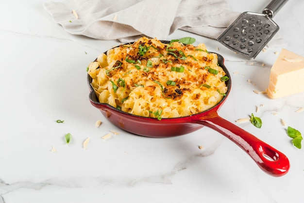 Mac and cheese, american style macaroni pasta with cheesy sauce and crunchy breadcrumbs topping, in portioned pan, white marble table, copyspace