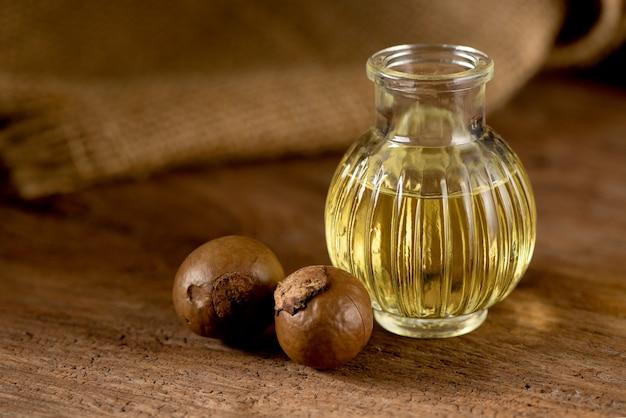 Макадамия, сухофрукты и масло на фоне природы.