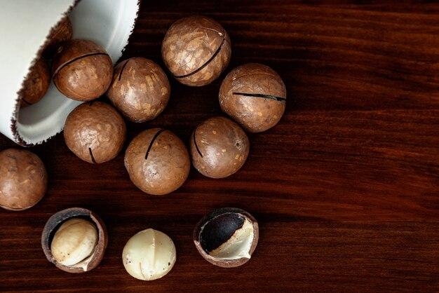 木製のテーブルにマカダミアナッツ。殻付きおよび殻なしのマカダミアナッツ。スーパーフードと健康食品のコンセプト