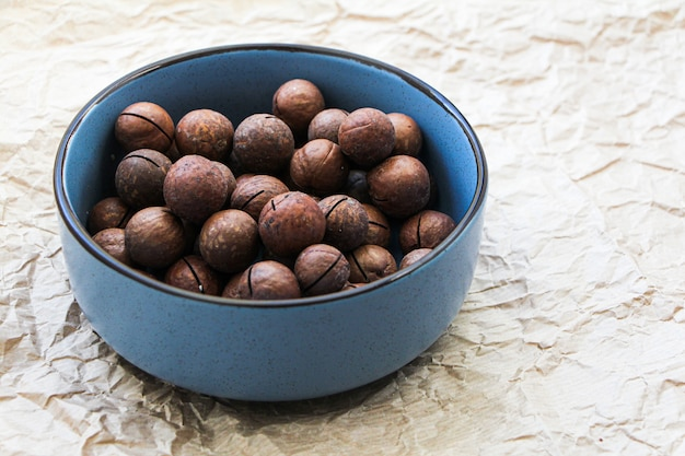 Macadamia nuts in a ceramic blue bowl on baking paper background. organic healthy food concept