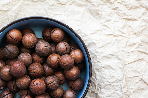 Macadamia nuts in a ceramic blue bowl on baking paper. organic healthy food concept