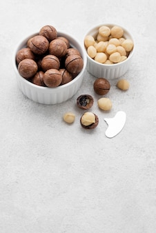 Macadamia nuts and chocolate in bowls copy space