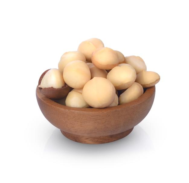 Орехи макадамия в деревянной миске на белом фоне вид сверху