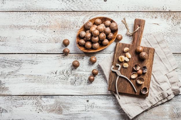 白い木製のテーブルの上のまな板のマカダミアナッツ