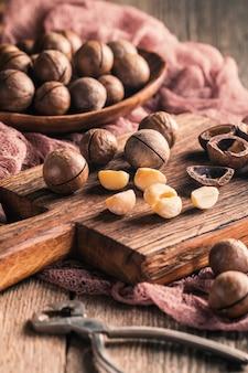 木製のテーブルの上のまな板のマカダミアナッツ