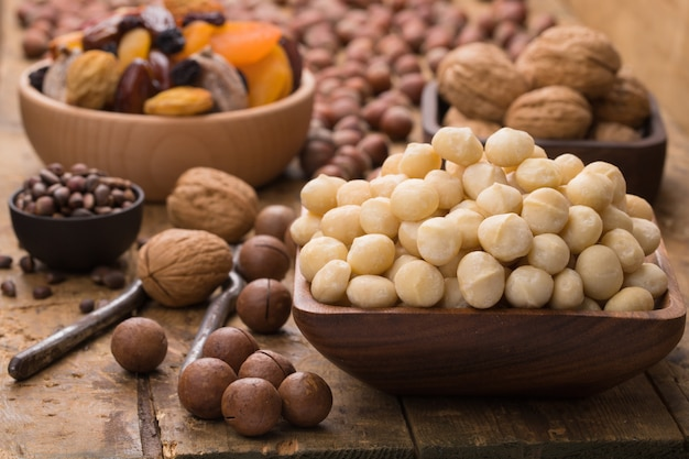 Macadamia nuts peeled in wooden bowl on table, grunge style.